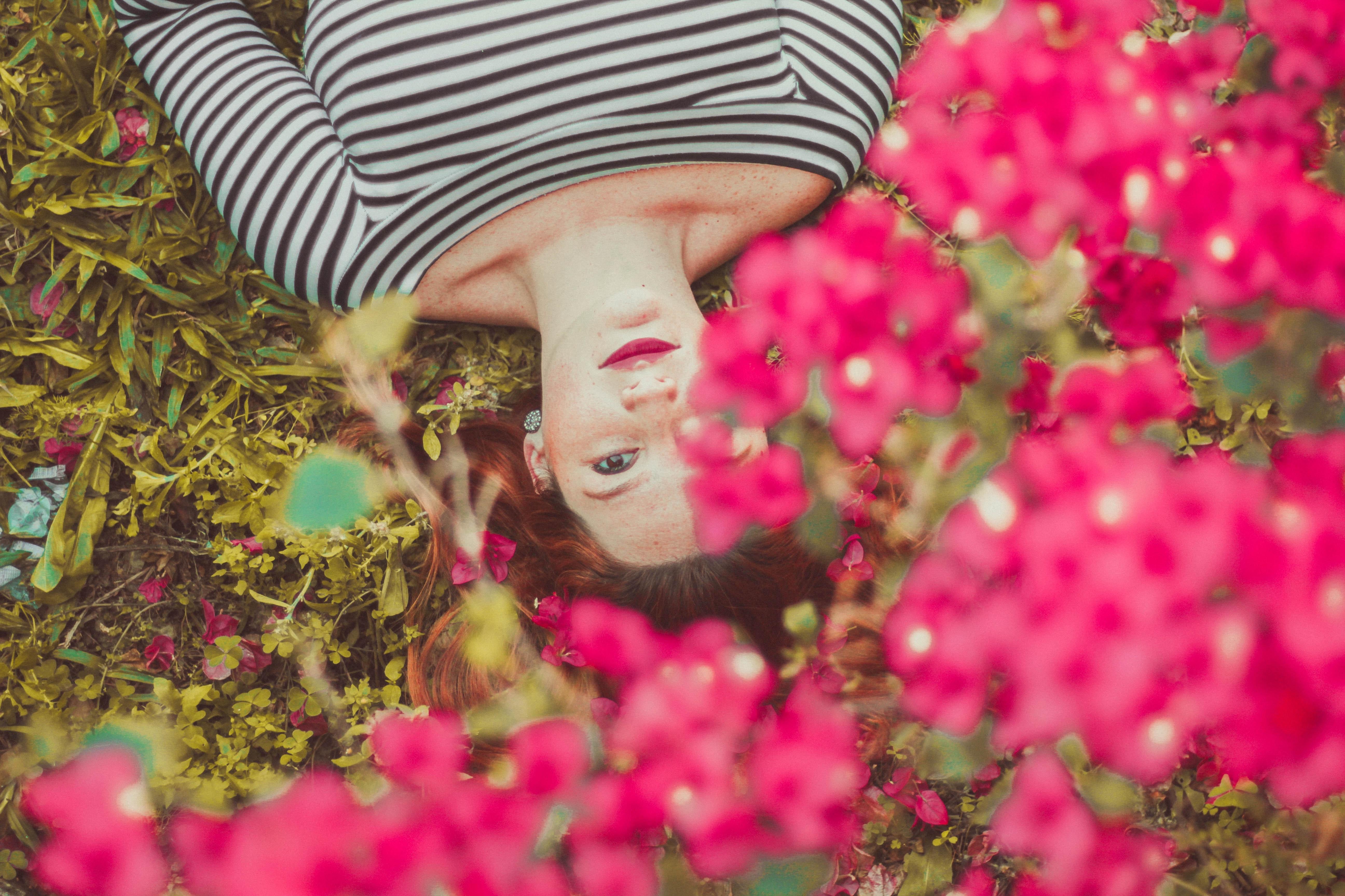 perspectiva superior de mulher deitada na relva com flores a olhar para a cima vestida com camisola branca às riscas pretas