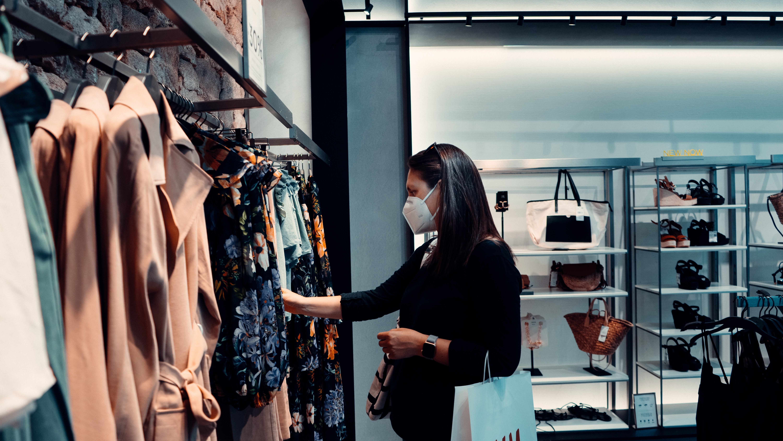 mulher de máscara social a escolher roupa num cabide de uma loja de roupa feminina