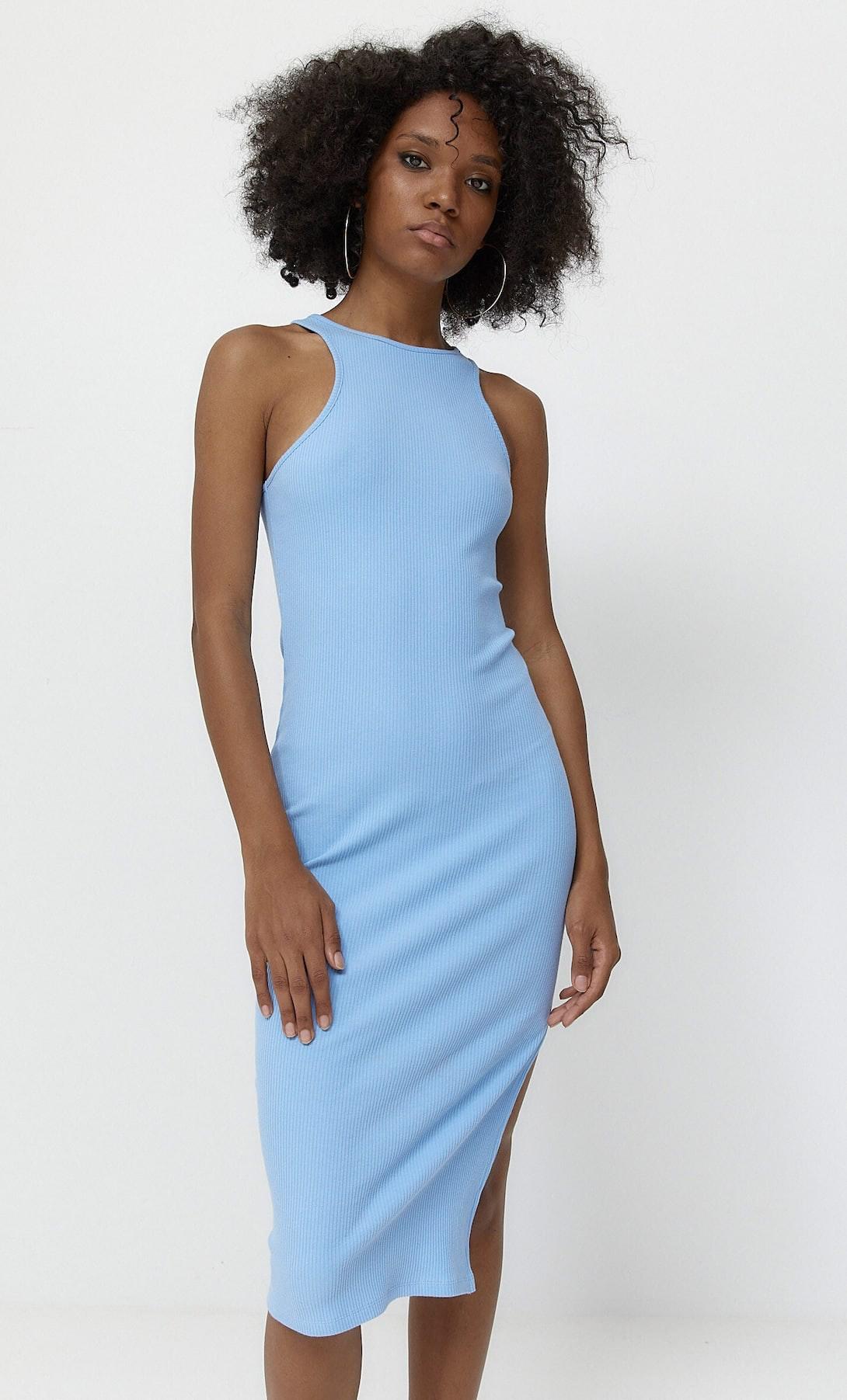 mulher de etnia africana com vestido da Stradivarius azul e comprido