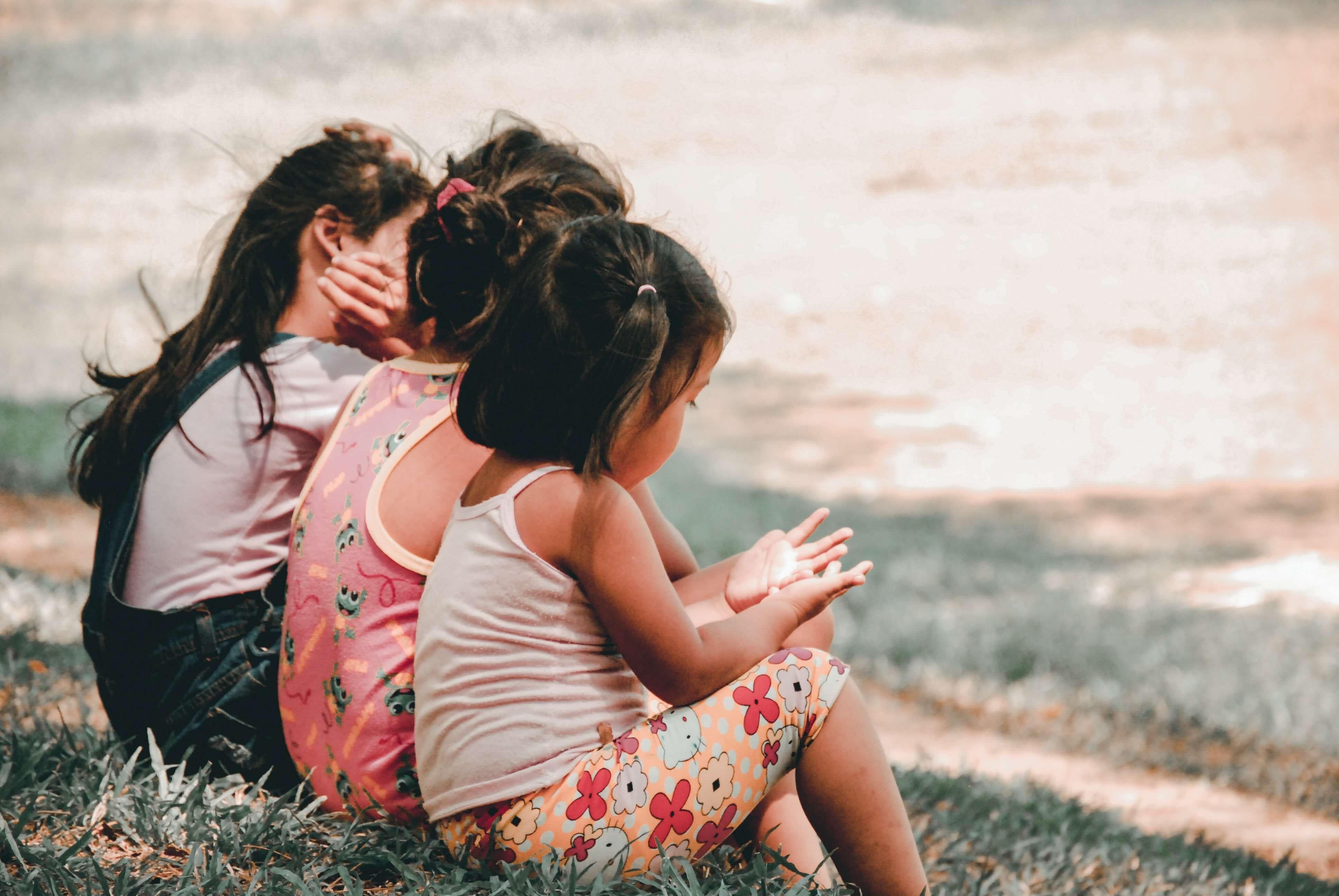 3 meninas sentadas na relva