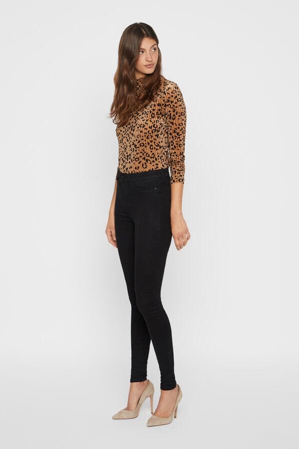 mulher vestida com blusa com padrão tigresa da Springfield, calças pretas e salto alto bege