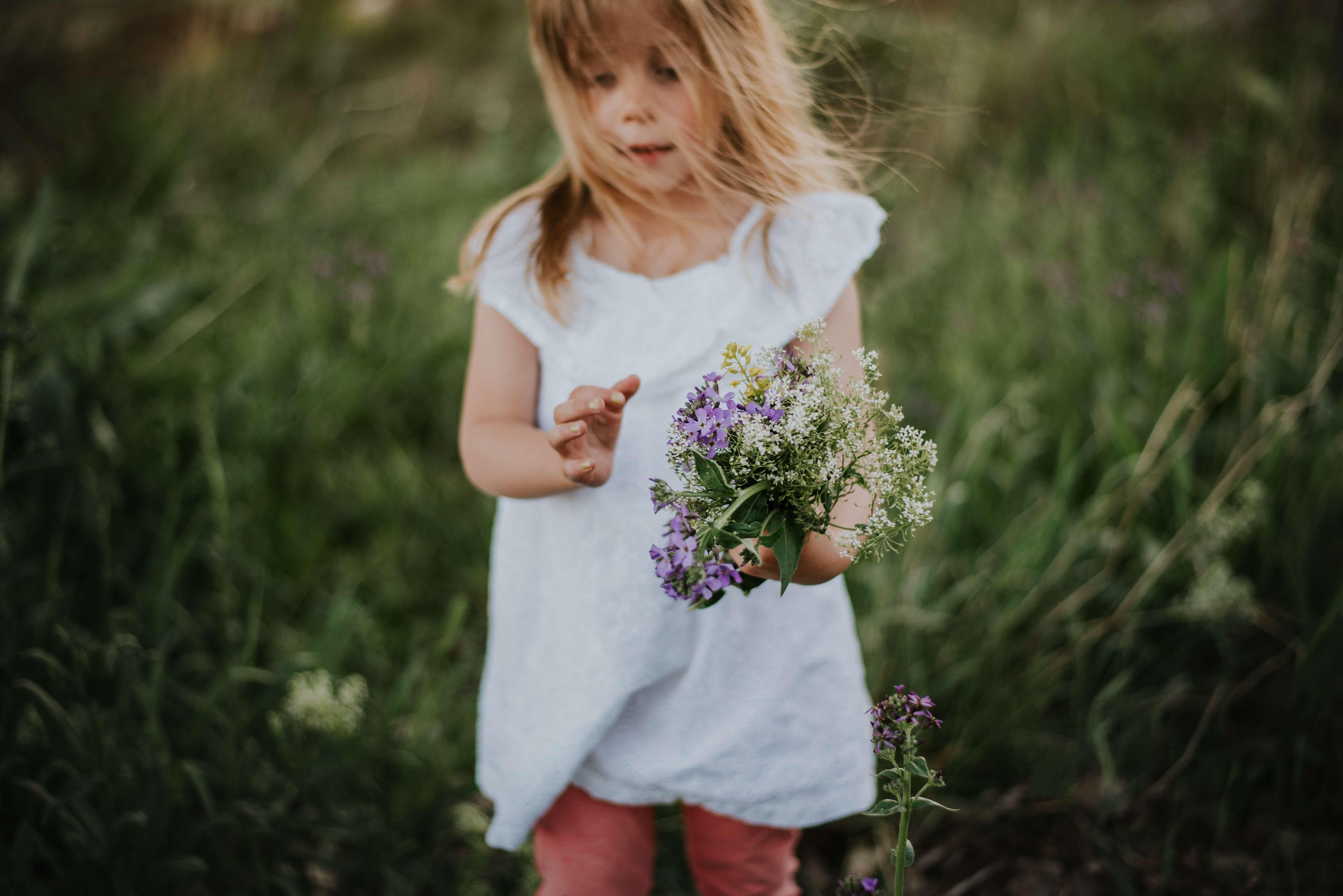 criança com flores na mão