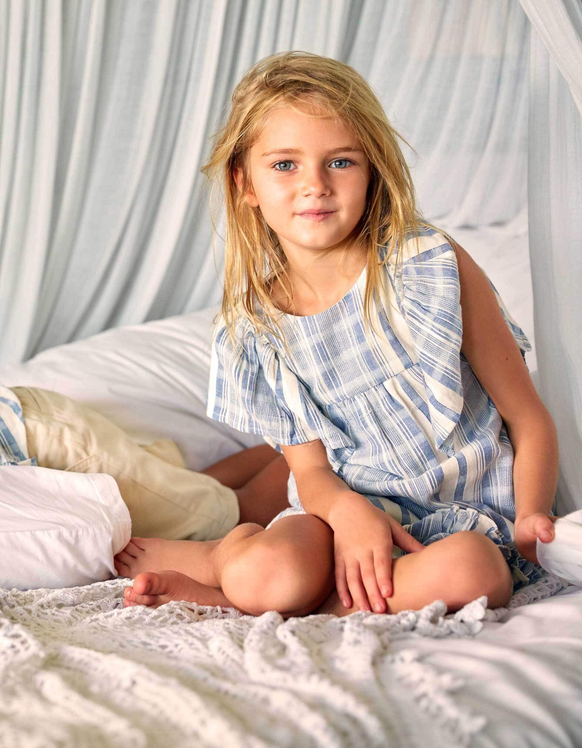 menina sentada na cama com vestido branco e azul da zippy